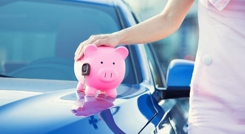 A woman has her hand on a piggy bank with car keys sitting on top of her new car. She used no credit car loans in Indianapolis to buy it.