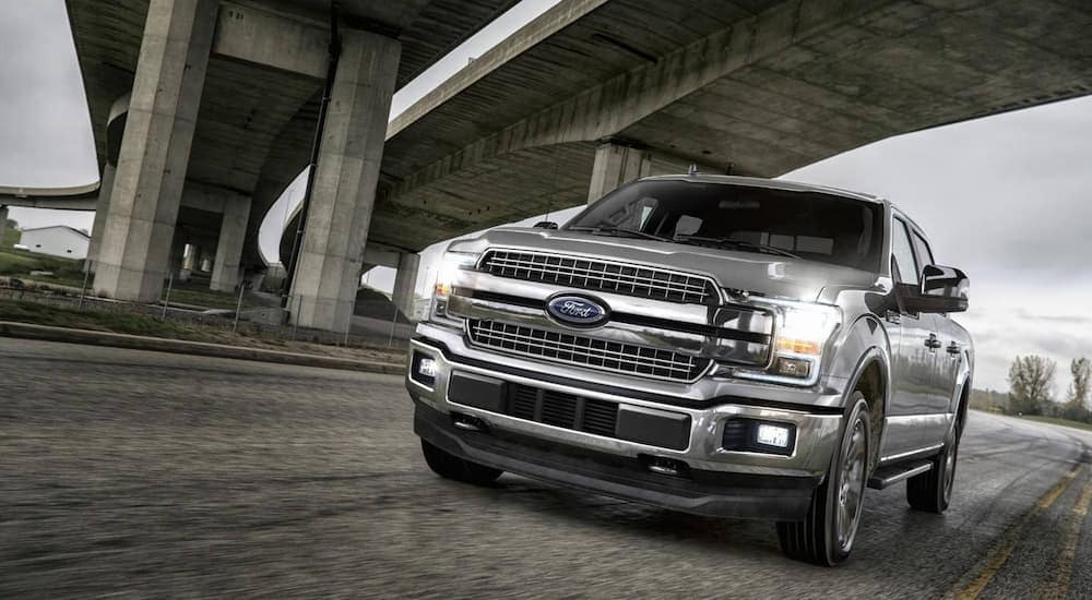 A silver 2018 Ford F-150 is driving under a bridge. The F-150 is one of several options for used Ford trucks in Columbus.