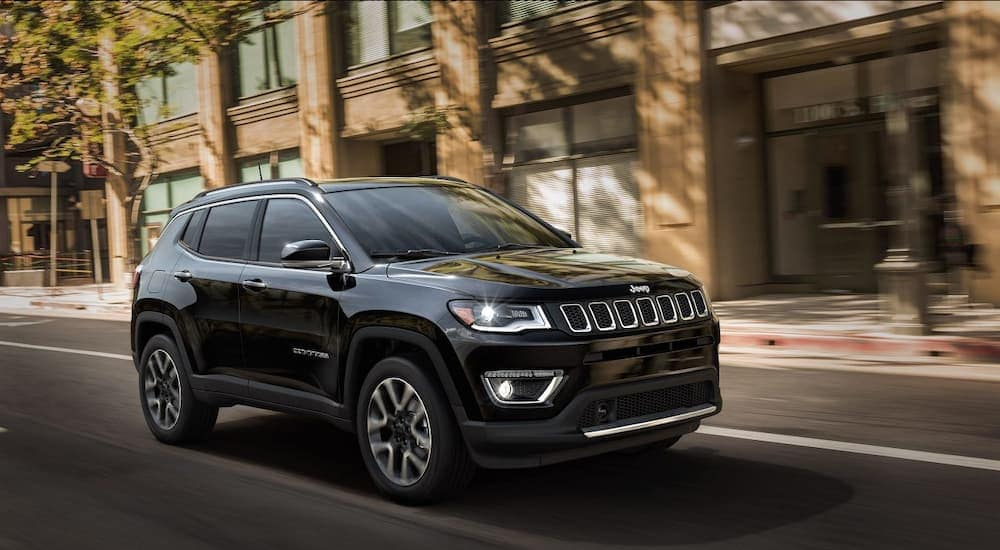 A black 2018 Jeep Compass is driving along a city block.