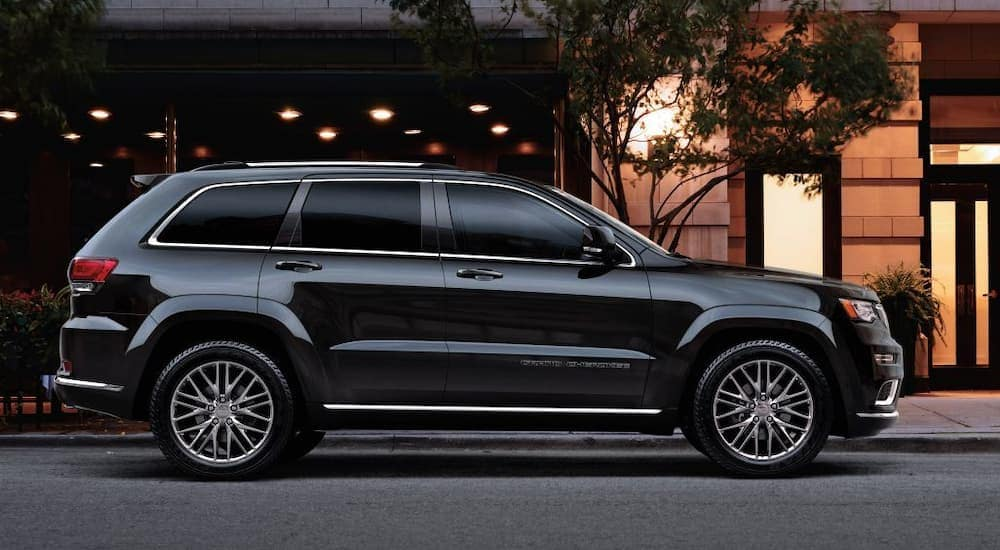 A black 2018 Jeep Grand Cherokee is parking outside a building a night. The Grand Cherokee is popular among used Jeeps for sale in Indianapolis.