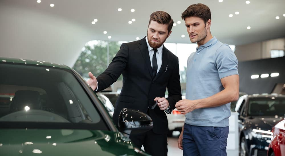 A frowning salesman is trying to show a concerned male shopper a car at a Buy Here Pay Here in Columbus, Ohio.