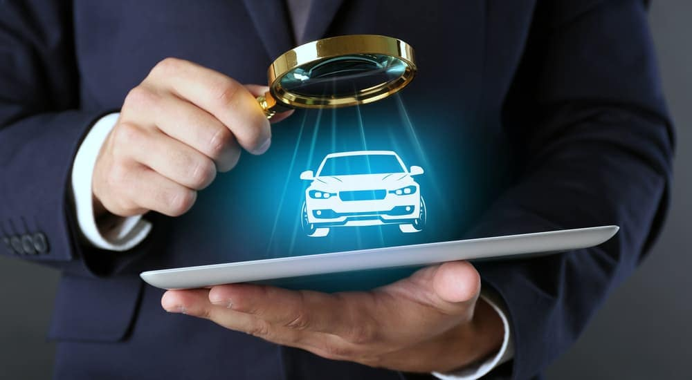 A close up of a man holding a tablet and a magnifying glass with a virtual car is searching for an alternative to Buy Here Pay Here in Columbus Ohio.