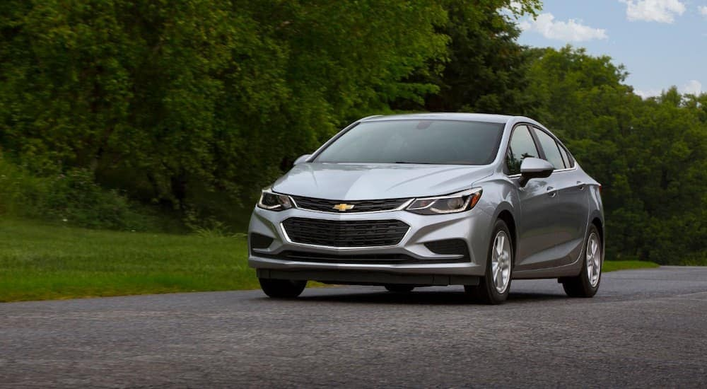 A silver 2017 Chevy Cruze is driving along a tree lined road after being purchased from an alternative to Columbus used car dealers.