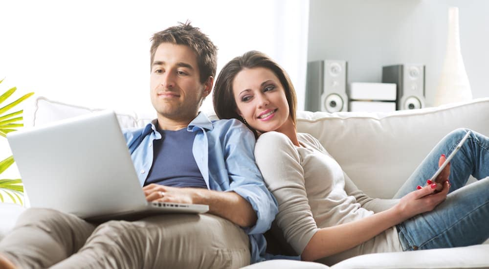 A couple on the couch is on a laptop looking for alternatives to Columbus used car dealers.