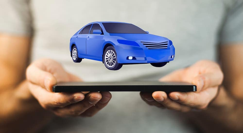 A man is holding a phone with a virtual blue car hovering over it. Online.cars is an alternative to Columbus used car dealers.