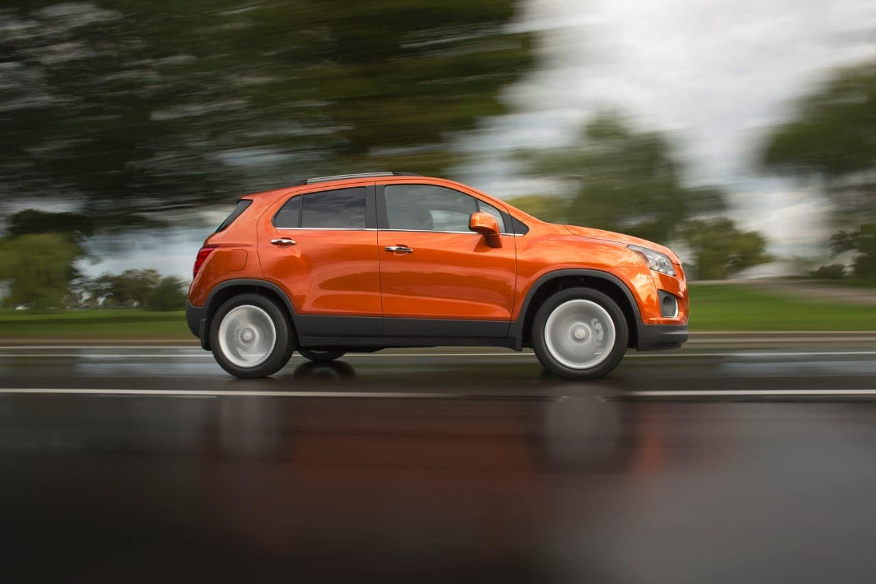 An orange 2016 Chevy Trax, a popular model for used Chevy SUVs for sale in Indianapolis, IN, is driving on a wet road.