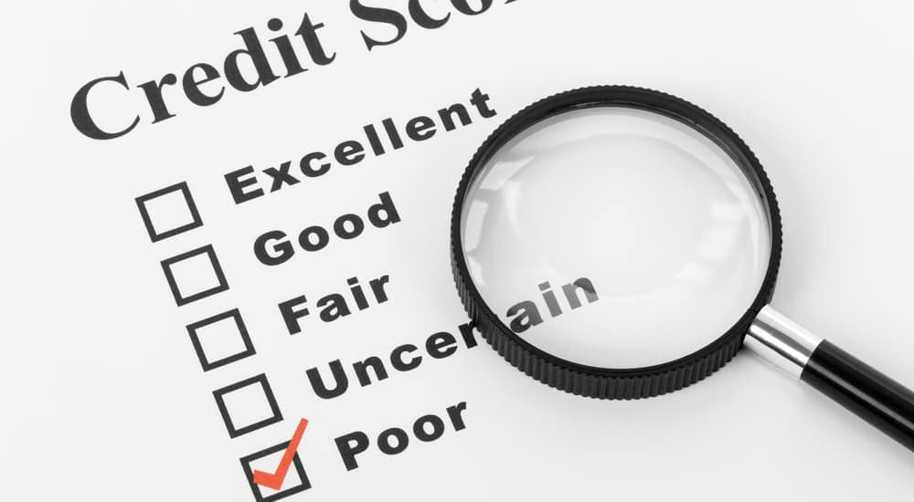 'Poor' is checked off on a list of credit scores with a magnifying glass.