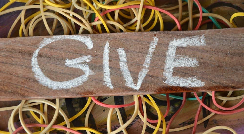 'Give' is written on a piece of wood with chalk.