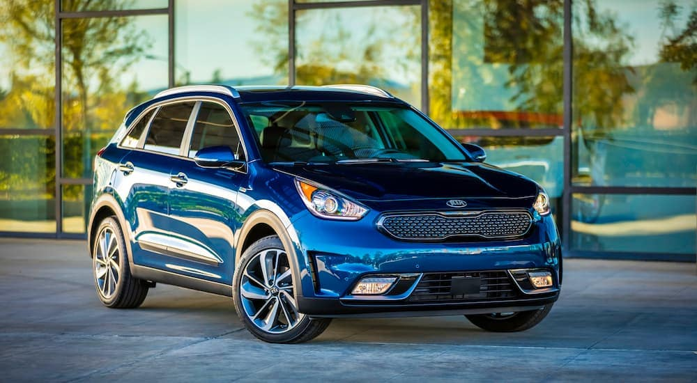 A blue 2018 Kia Niro is parked in front of glass near Indianapolis, IL.