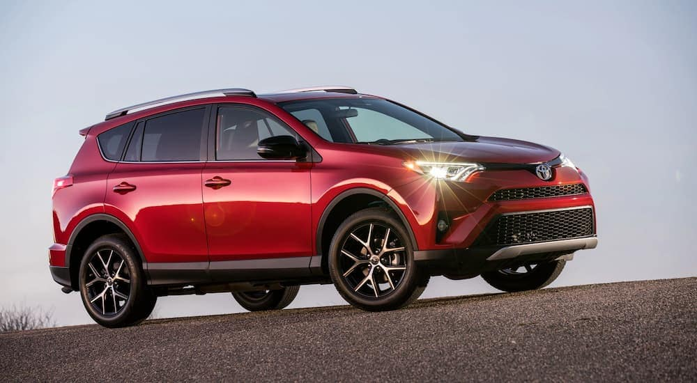 A red 2017 Toyota RAV4, popular among used SUVs for sale in Indianapolis, IN, is parked on an incline.