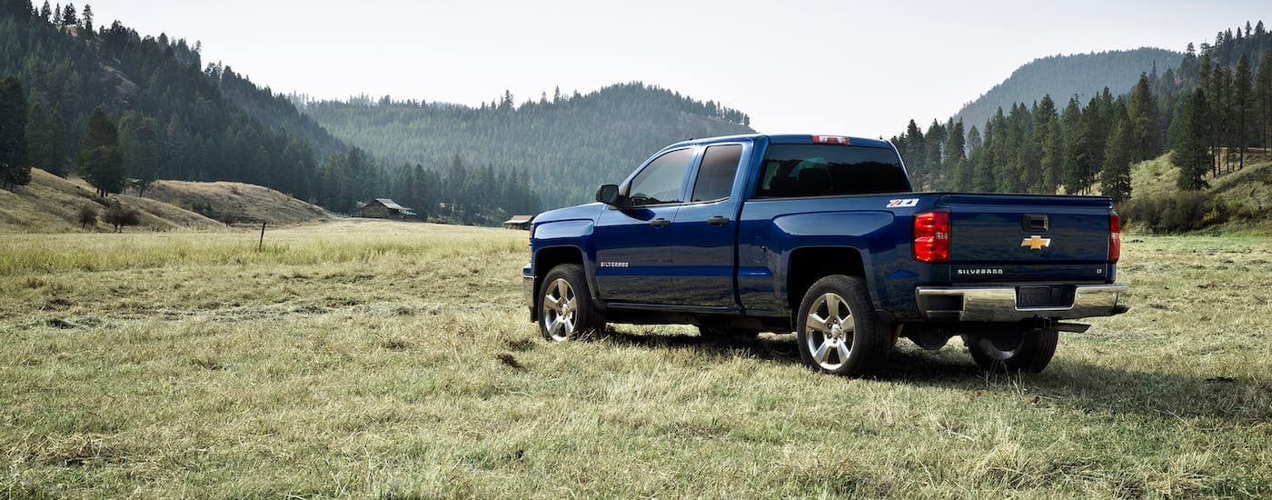A popular used truck for sale in Columbus, OH, a blue 2014 Chevy Silverado LTZ Z71 is parked in a field overlooking mountains and a clear blue sky.