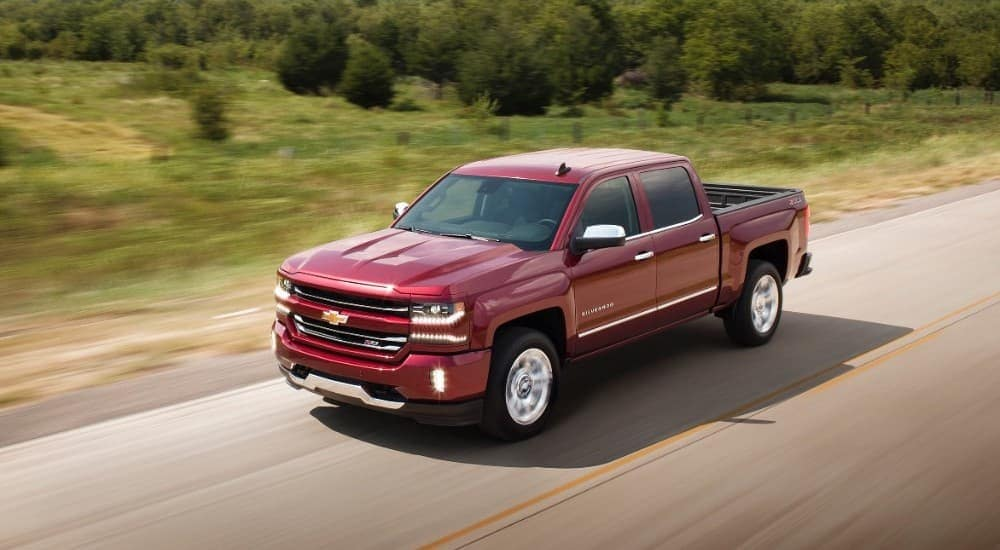 A red 2017 Chevy Silverado 1500 is driving on a road past blurred grass and trees.