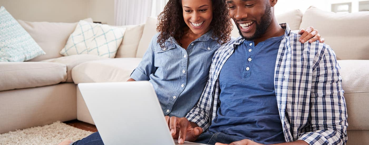 A couple is shopping for used trucks for sale in Columbus, Ohio, online on a laptop.