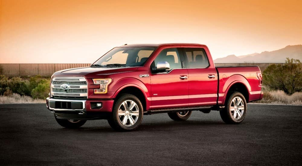 A red 2015 Ford F-150, popular among used trucks for sale in Columbus, OH, is parked with a low sun behind it.