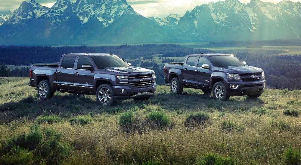 A 2018 Chevy Silverado is parked next to a 2018 Colorado with mountains behind them.