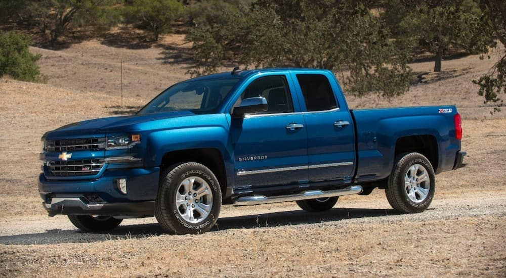A blue 2018 Chevy Silverado 1500, one of the popular used trucks for sale in Columbus, OH, is parked on a dirt road.