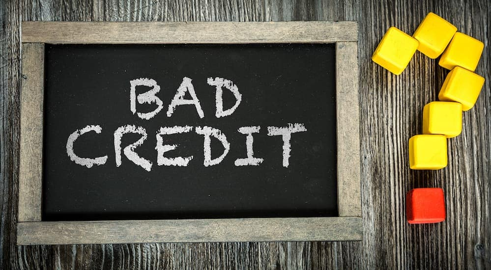 Bad credit is written on a chalkboard next to a block question mark.