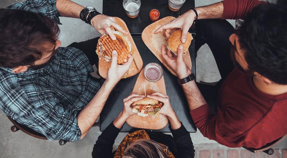 Three people are eating burgers at a small table which is shown from above.