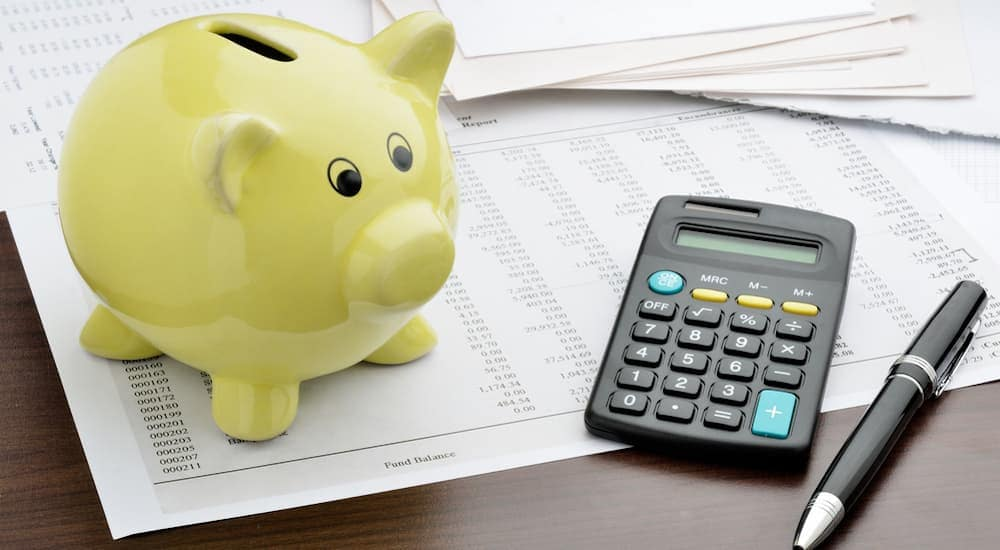 A green piggy bank is next to a calculator for budgeting when an auto loan with bad credit in Columbus is needed.