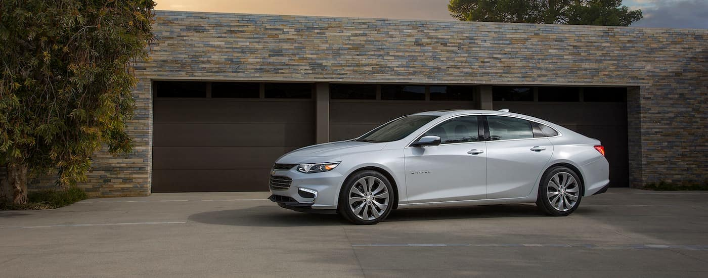 A white 2016 Chevy Malibu is parked in front of a garage in Columbus, OH.