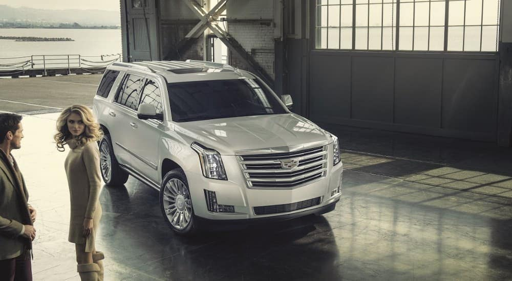 A couple who buy used cars in Columbus, OH are next to a white 2017 Cadillac Escalade in a warehouse.