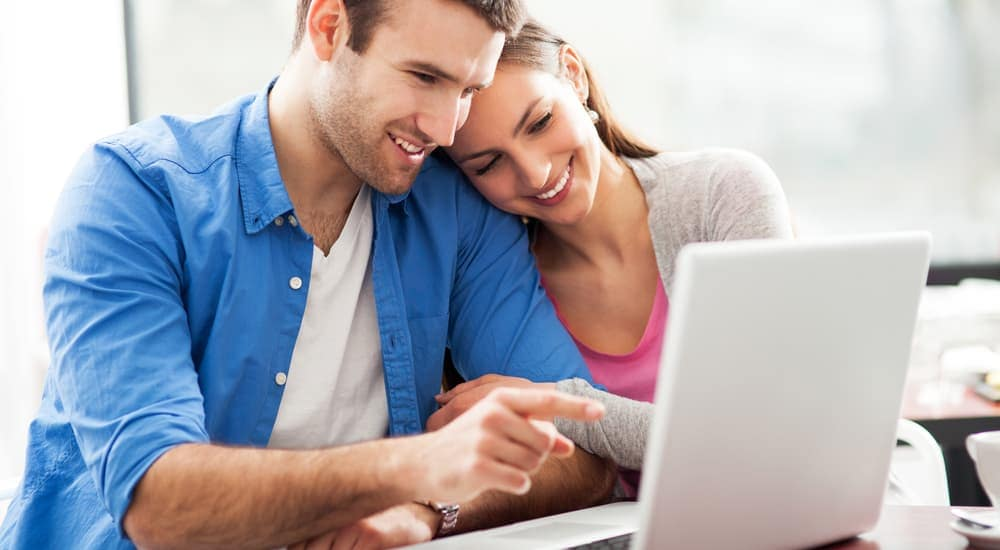 A smiling couple is on their laptop to buy used cars and use the 'Find Your Dream Car' tool.
