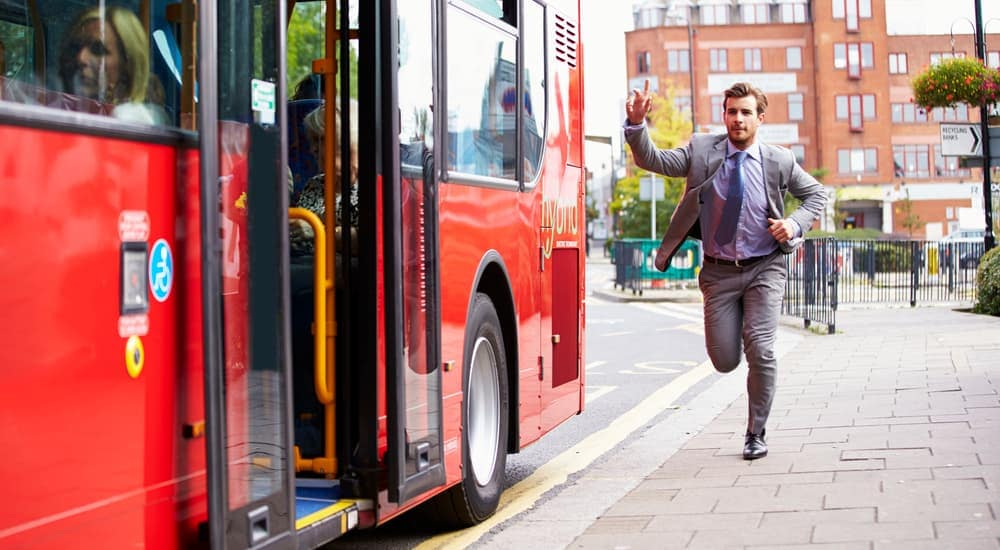 A man is running towards a red city bus.