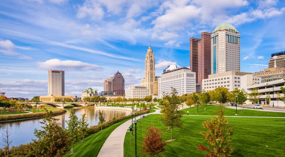 The Columbus, OH skyline is shown from a park.
