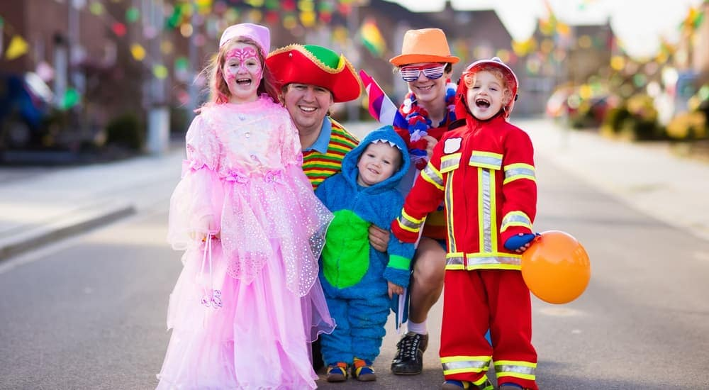 A family is dressed up in costume at a trunk-or-treat event where some cars were purchased with a bad credit car loan in Columbus.