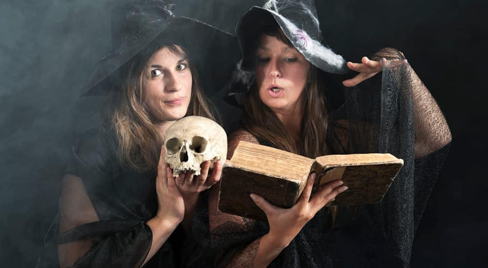 Two women dressed as witches are reading from a spell book.
