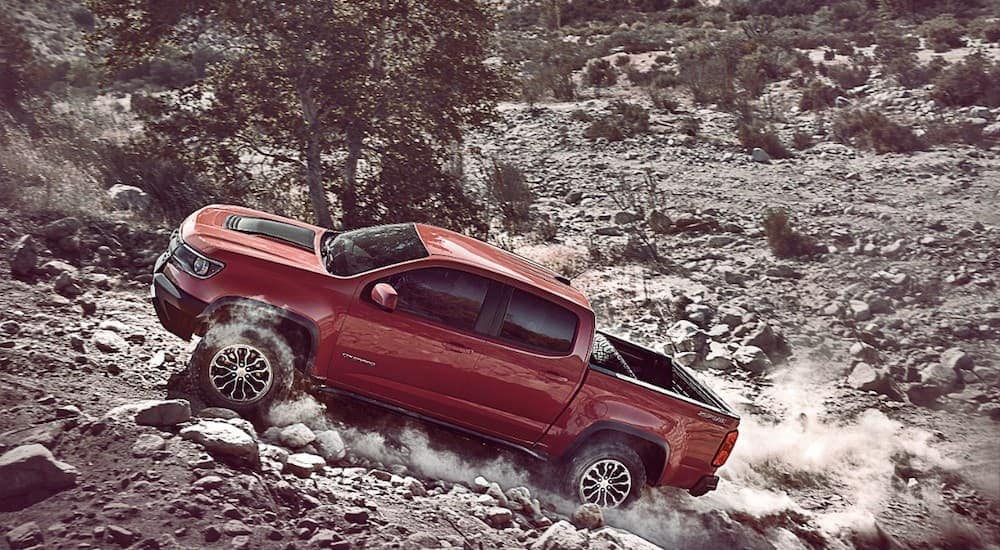 A red 2017 Chevy Colorado ZR2, popular among consumers who buy used cars in Columbus, OH that are off-road ready, is climbing a rock hill.