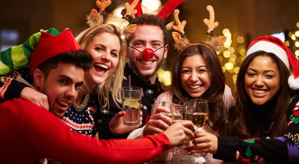 A group of friends are dressed up for the Christmas holiday in ugly sweaters and antlers, toasting their drinks and smiling.