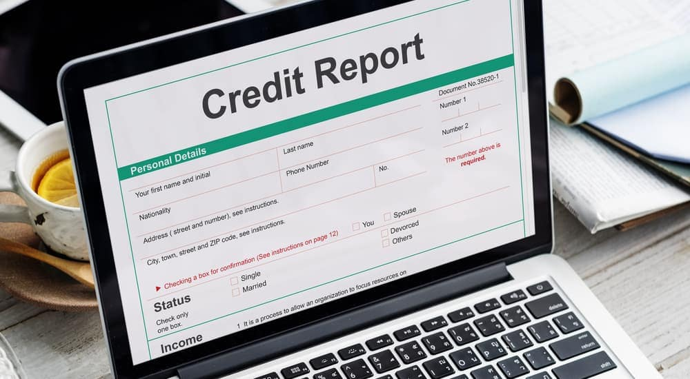A credit report is shown on a laptop.