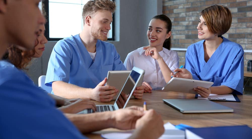 Nursing students in scrubs are on laptops and chatting.