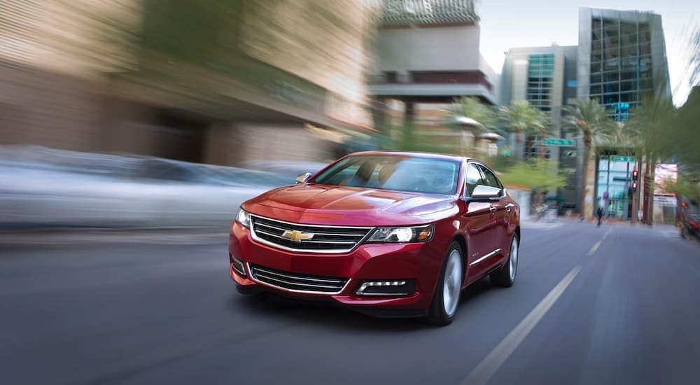 A red 2016 Chevy Impala is driving down a city street after leaving a used car lot near me in Indianapolis, IN.