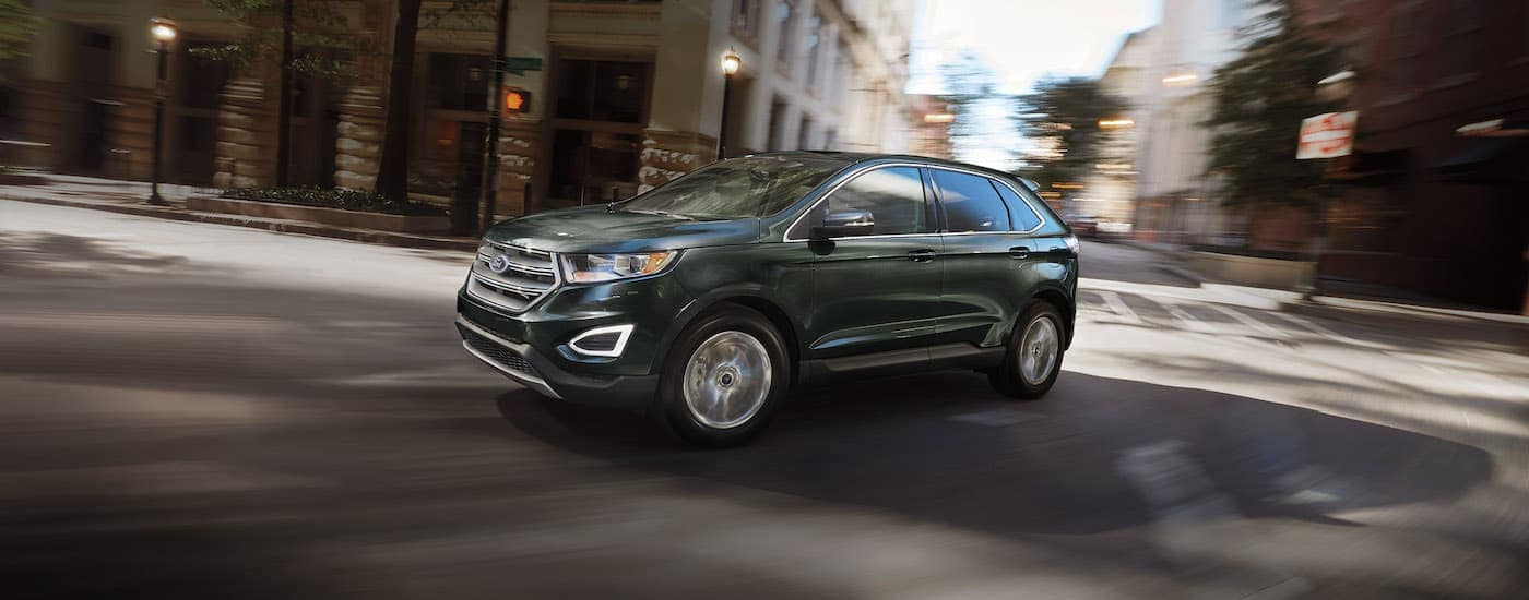 A dark grey 2016 Ford Edge is rounding a corner on a city street.