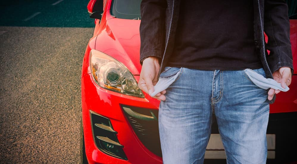 A man with inside out empty pockets is standing front of a car looking for No Credit Car Lots in Indianapolis, IN.