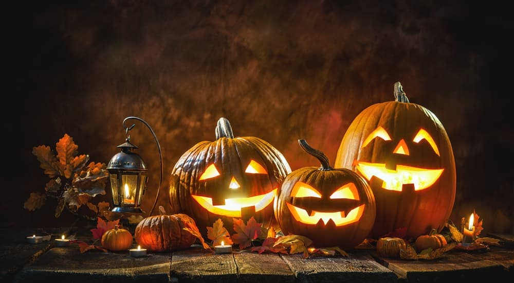 Three smiling carved pumpkins are lit up next to a lantern.
