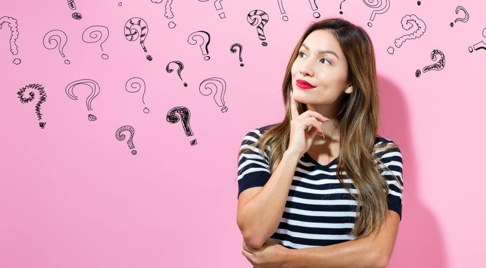A woman has her arms crossed with question marks behind her.