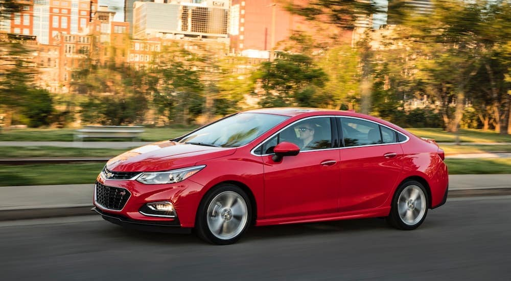 A red 2016 Chevy Cruze is driving past a city park.
