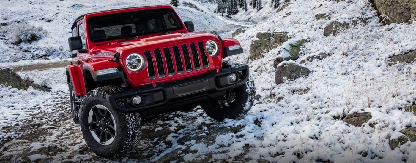 A red 2019 Jeep Wrangler is on a snowy trail.