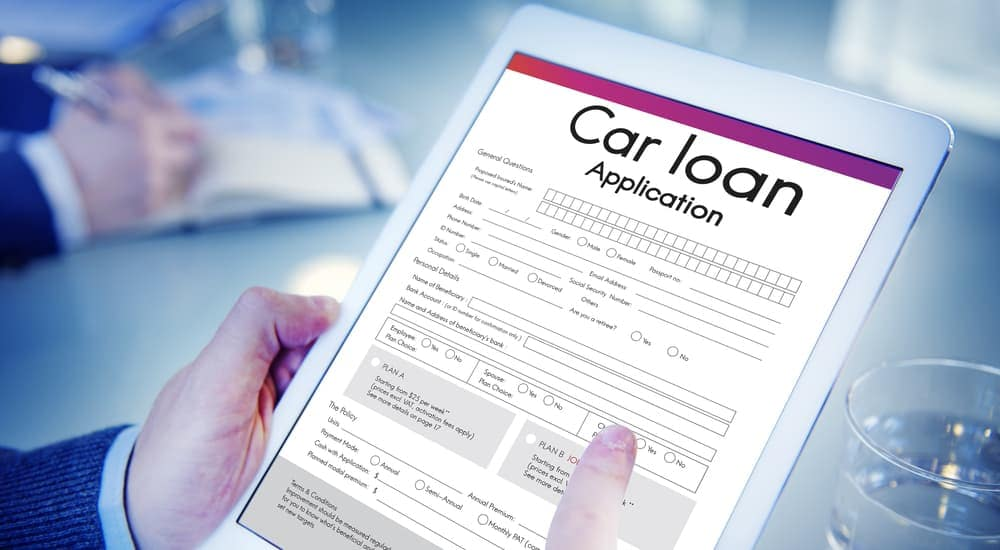 A man is looking at a car loan to decide what is better for him, a Buy Here Pay Here vs traditional Loan in Indianapolis, IN.