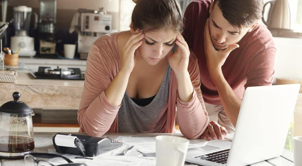 A couple is stressed out while looking at their credit scores.