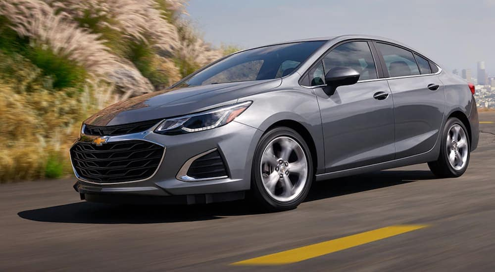 A grey 2019 Chevy Cruze, a car you may be able to get with poor credit car loans, is driving on a road outside of Columbus, OH.