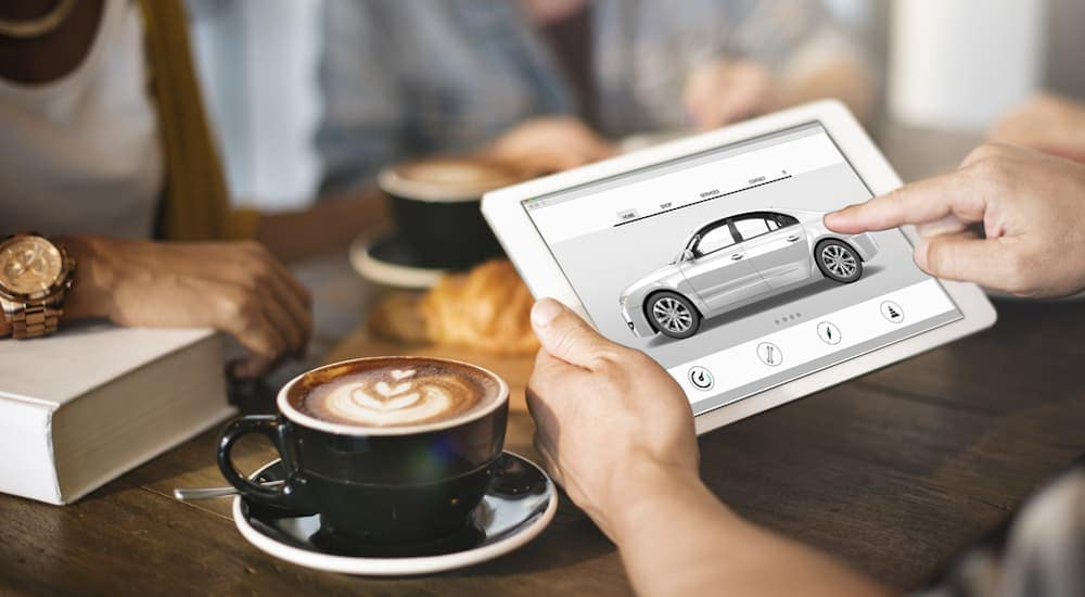 Someone is having a coffee while looking up cars to buy online.