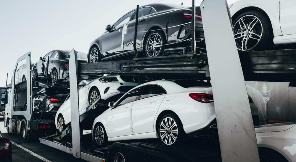 A truck from an online car dealer delivery service has cars on its trailer.