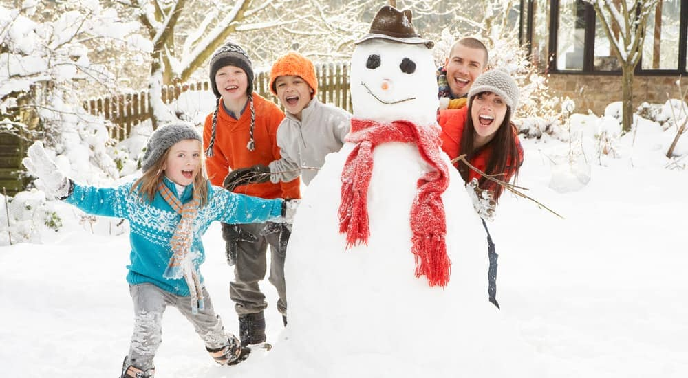 A family is smiling while making a snowman.