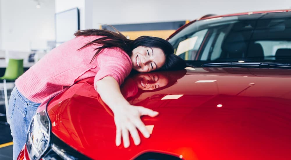 After searching 'what type of credit score to get a car near Columbus', a woman is hugging the car of her dreams.