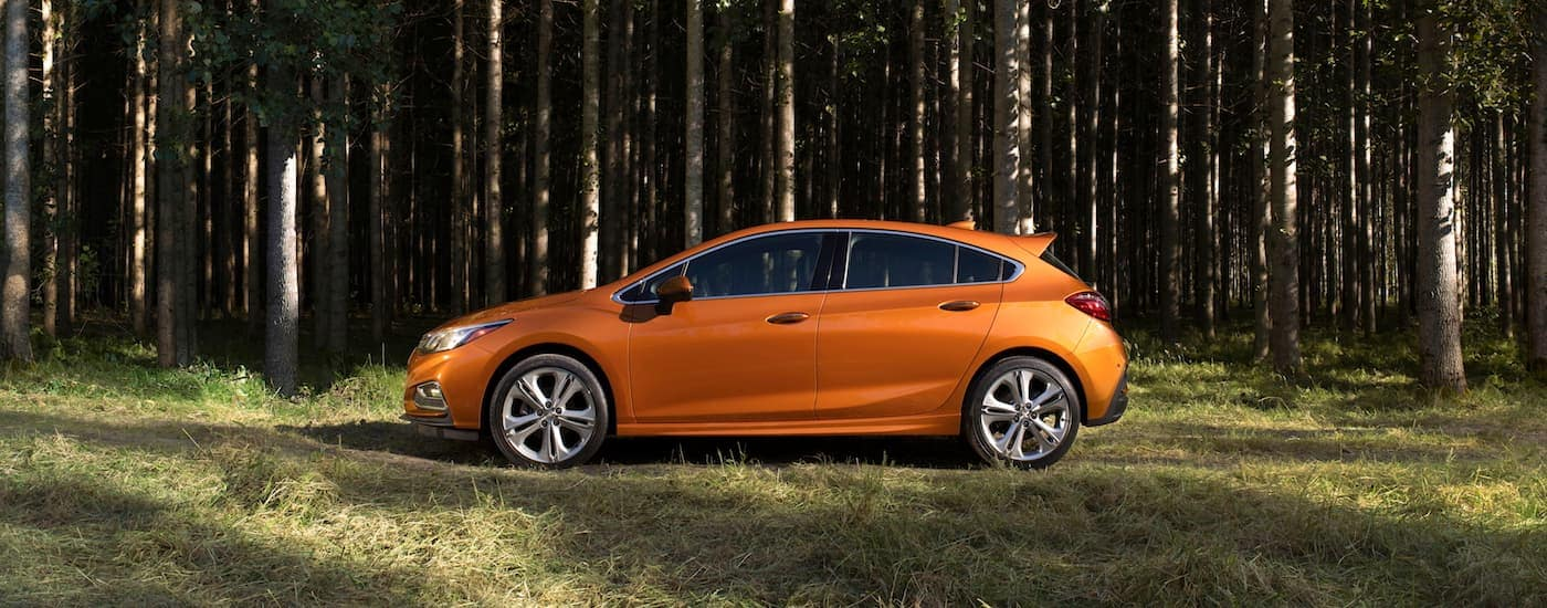 A side view of an orange 2018 Chevy Cruze hatchback is parked on a trail in the woods.