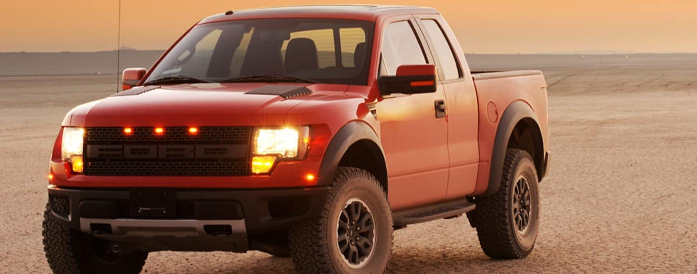 A red 2010 Ford Raptor is parked on flat dirt with mountains in the distance at dusk.